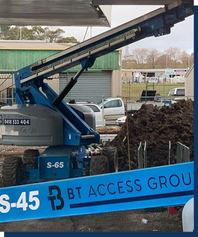 A boom lift with BT Access Group branding sitting under a root